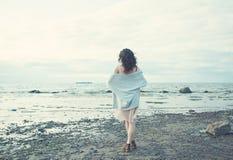 Femme en bonne santé se reposant sur le fond bleu de mer et de ciel Photographie stock libre de droits