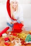 Femme en cadeaux de Noël d'emballage de chapeau de Santa photos stock