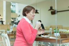 Femme en café avec la tasse de café Photo stock