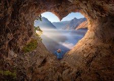 Femme en caverne de forme de coeur observant le canyon brumeux au matin Photo libre de droits