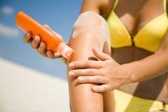 Femme en crème protectrice de souillure de bikini Photo stock