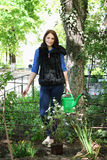 Femme en fleurs de jardinage des eaux Photos stock