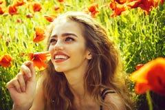 Femme en fleurs de pavot jolie femme ou fille heureuse dans le domaine du clou de girofle Photographie stock