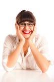 Femme en glaces avec des coudes sur le bureau, souriant photographie stock libre de droits