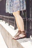 Femme en jupe bleu-clair et sandales plates brunes, avec les jambes nues Photo stock