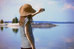 Femme en mer prenant la photo Photos libres de droits
