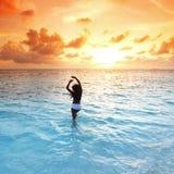 Femme en mer sur le coucher du soleil Photo libre de droits
