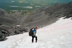 Femme en montagne restant sur la neige Photographie stock