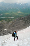 Femme en montagne restant sur la neige Photo libre de droits