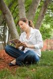 Femme en parc avec le comprimé mobile Photographie stock