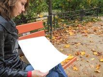 Femme en parc d'automne poussant des feuilles par les pages de l'album blanc Femme poussant des feuilles par les pages La femme s Image stock