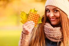 Femme en parc d'automne tenant des médecines de vitamines Photographie stock libre de droits