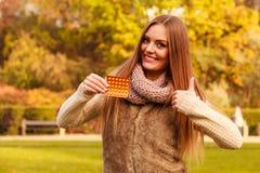 Femme en parc d'automne tenant des médecines de vitamines Image libre de droits