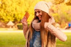 Femme en parc d'automne tenant des médecines de vitamines Photos libres de droits