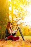 Femme en parc d'automne utilisant la lecture de tablette Photographie stock