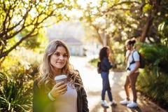 Femme en parc jugeant un café en verre Image stock