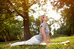 Femme en parc vert faisant des exercices physiques Photographie stock