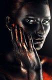 Femme en peinture avec la main sur la joue photo stock