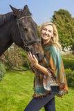 Femme en Poncho Leading Her Horse Images stock