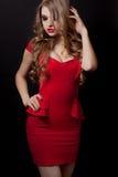 Femme en portrait rouge de robe d'isolement sur le fond noir Photo libre de droits