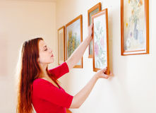Femme en rouge accrochant les photos d'art photo stock