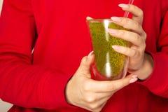 Femme en verre rouge de jus de kiwi de participation de chandail L'espace pour le texte photo libre de droits