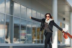 Femme en verres de soleil une veste en cuir noire, jeans noirs avec des paniers, appréciant la promenade devant une fenêtre de ma Image libre de droits