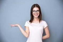 Femme en verres présentant quelque chose sur la main Image libre de droits