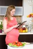 Femme enceinte à l'aide d'une tablette dans la cuisine Photo stock