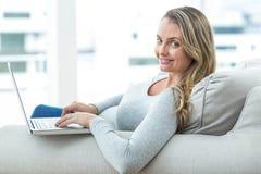 Femme enceinte à l'aide de l'ordinateur portatif Photos libres de droits