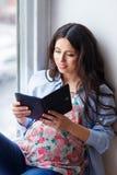 Femme enceinte à l'aide de la tablette photos stock