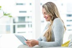 Femme enceinte à l'aide de la Tablette de Digital Photo stock