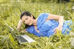 Femme enceinte à l'aide de l'ordinateur portable sur le pré images libres de droits