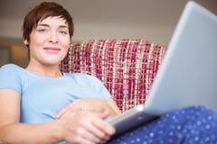 Femme enceinte à l'aide de son ordinateur portable Photos libres de droits