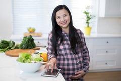 Femme enceinte à l'aide du comprimé numérique dans la cuisine Image stock