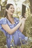 Femme enceinte à l'aide du comprimé sur le pré photo stock
