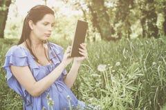 Femme enceinte à l'aide du comprimé sur le pré images stock
