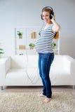Femme enceinte écoutant la musique Photos libres de droits