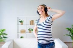 Femme enceinte écoutant la musique Photo libre de droits