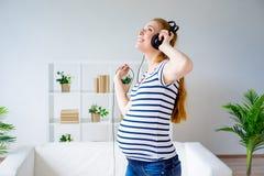 Femme enceinte écoutant la musique Photographie stock libre de droits