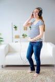Femme enceinte écoutant la musique Images stock