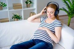 Femme enceinte écoutant la musique Images libres de droits