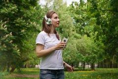 Femme enceinte écoutant la musique sur des écouteurs Photo stock