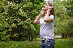 Femme enceinte écoutant la musique sur des écouteurs Photographie stock