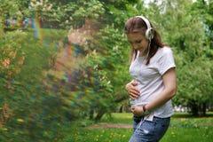 Femme enceinte écoutant la musique sur des écouteurs Photographie stock libre de droits