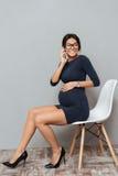 Femme enceinte étonnante d'affaires parlant par le téléphone Photographie stock