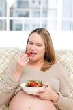 Femme enceinte affamé mangeant des fraises Photographie stock libre de droits