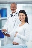 Femme enceinte agissant l'un sur l'autre avec le docteur image stock