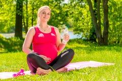 Femme enceinte 25 ans d'heureuse pendant l'été le parc Photographie stock