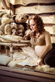 Femme enceinte attirante se trouvant sur la fourrure et le livre de lecture Image libre de droits